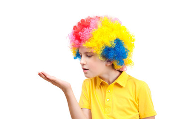 The boy in clown wig blowing on the palm