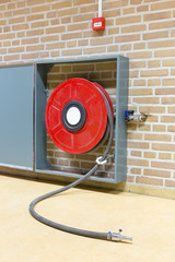 Red fire hose on reel at wall