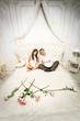 couple in love sitting on luxurious bed decorated with roses