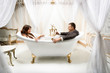 clothed man and woman having fun in luxurious bath