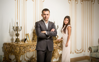 handsome man in suit posing at classic interior with woman