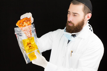 Bearded doctor holding pizza in plastic bag.