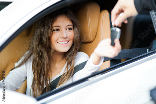 Young woman receiving the keys of her new car