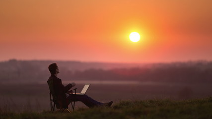 Man with PC at the hill top, sunset time lapse