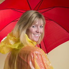 Woman in yellow poncho holding red umbrella
