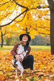 Happy young woman playing with dog outdoors in autumn - 74155603