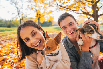 Portrait of smiling young couple with dogs outdoors