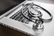 Leinwandbild Motiv Medical Stethoscope Resting on Laptop Computer