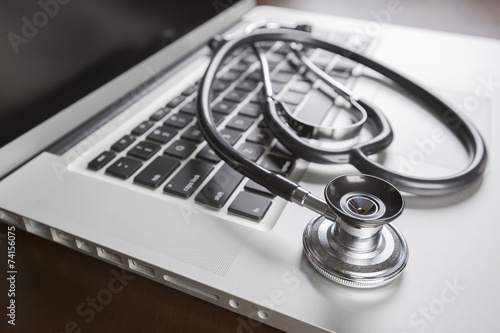 Medical Stethoscope Resting on Laptop Computer - 74156075