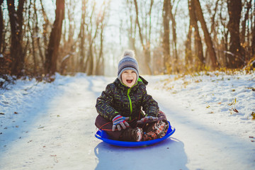 Boy in winter outdoors sledding