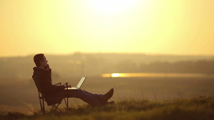 The man sit and work on the laptop on the top of the hill