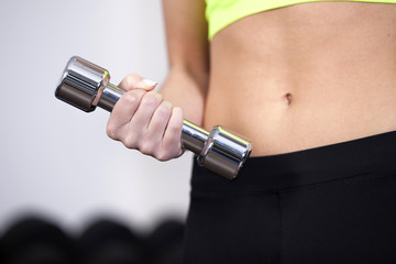Closeup of woman at the gym lifting free weights