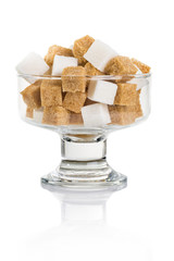 cubes of brown and white sugar in a glass vase