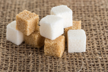 cubes of brown and white sugar on jute bags