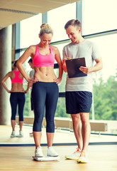 smiling man and woman with scales in gym