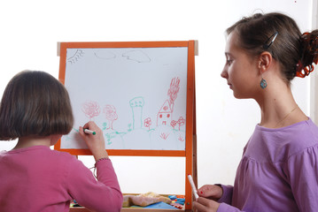 Youngs girls drawing on the white board