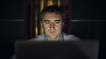 A middle aged man working at a computer in the lab.