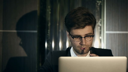 Young intelligent man smoking an electronic cigarette indoors.