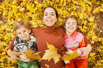 Mother and children playing outdoor with autumn leaves
