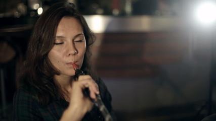 Girl enjoying smoking hookah in a night cafe