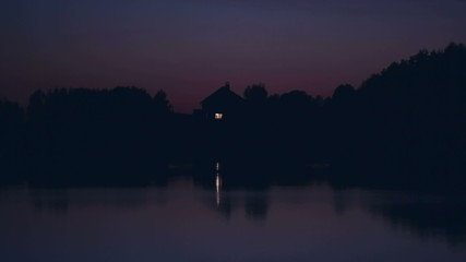 Lonely ascetic house on the lake at night