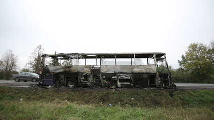 Burned-out passenger bus on the side of the road