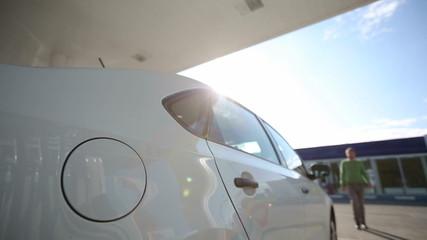 A man fills a white car quality biofuels at sunrise
