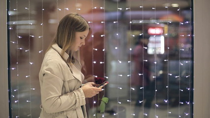 The girl with a rose in hand uses a smartphone girl writes sms.