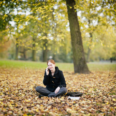 Woman Calling by Phone from an Autumn Park