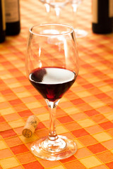Glass of red wine in the rustic tablecloth