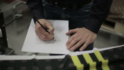 The man at the factory draws clothes