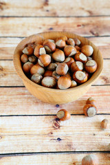 hazelnuts with shell in a wooden bowl