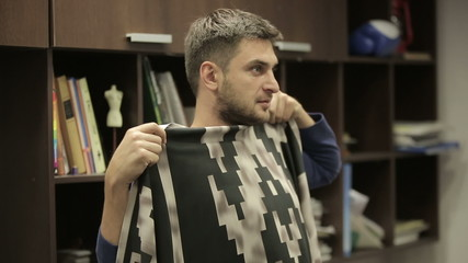 Man tries fabric for clothing. Office of the designer.