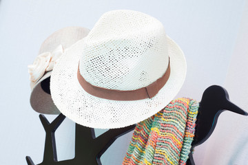 Bright colored scarf with hat hanging on a rack. in a dressing r