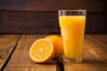 Orange fruit and glass of juice on brown wooden background