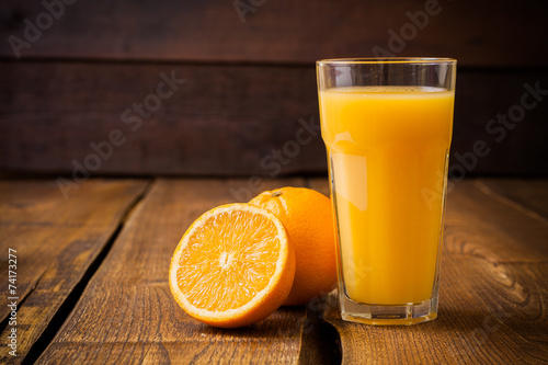 Foto op Aluminium Vruchten Orange fruit and glass of juice on brown wooden background