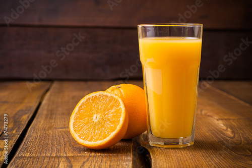 Orange fruit and glass of juice on brown wooden background - 74173279