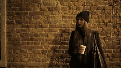 Girl teenager in the street at night drinking coffee and waiting