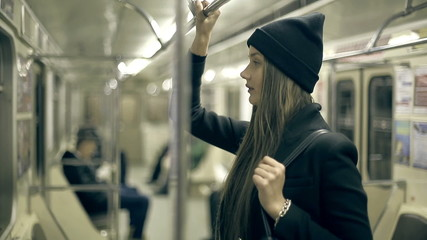 Teen girl rides the metro at night