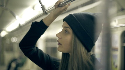 Teen girl rides the metro at night