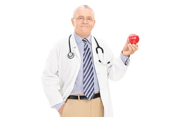 Mature doctor holding a ripe apple