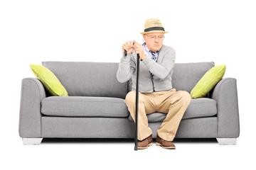 Worried senior gentleman sitting on a sofa