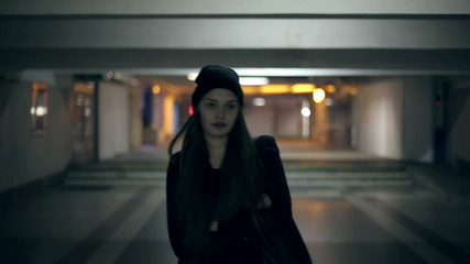 Girl teenager goes at night in the underpass