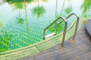 green swimming pool with teak wood flooring