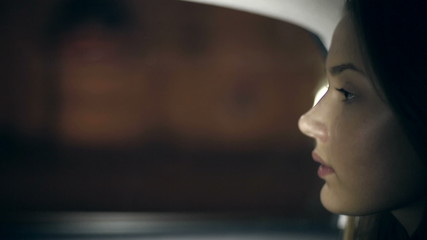 Girl rides in a taxi at night. Close up with bokeh