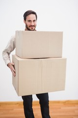 Smiling man holding a cardboard moving box
