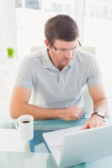 Casual businessman using his laptop at desk