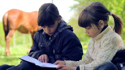 Two village boys reading a book on nature.