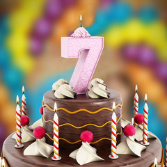 Birthday cake with number 7 lit candle