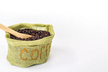 wooden spoon in a bag full of coffee beans